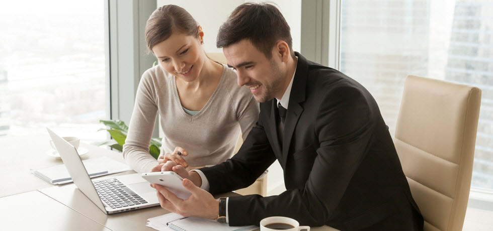 Office workers using digital tablet and laptop for planning event marketing SMS campaign