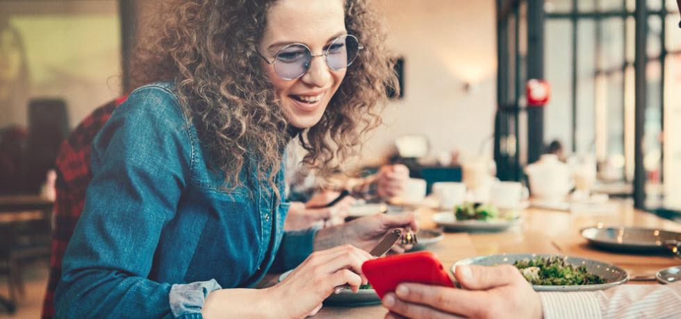 Woman looking smartphone in restaurant