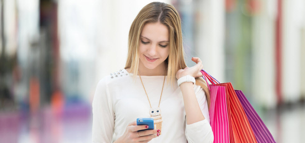 Young woman with shopping bags reading text message
