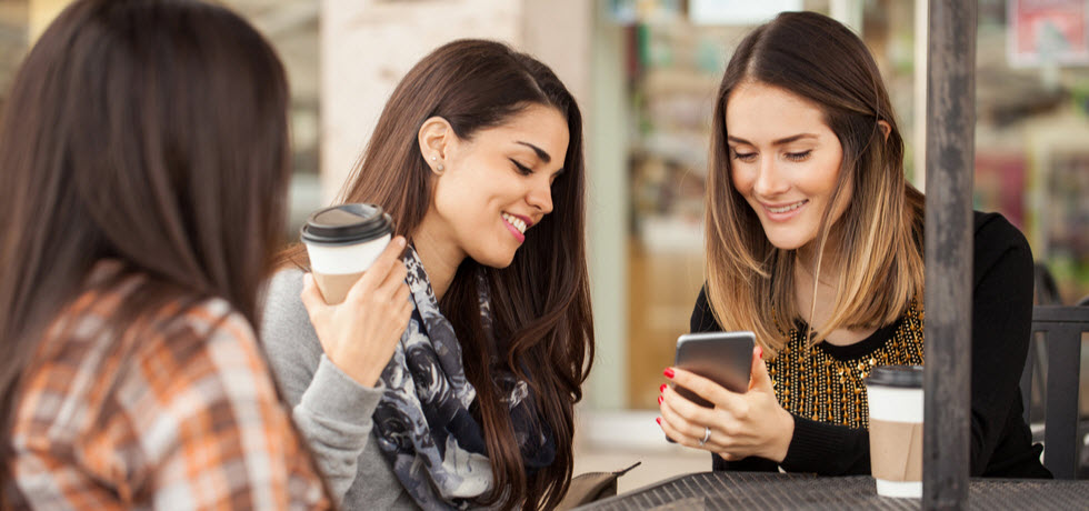 Pretty brunette showing a text message on her smartphone to her friends while having some coffee