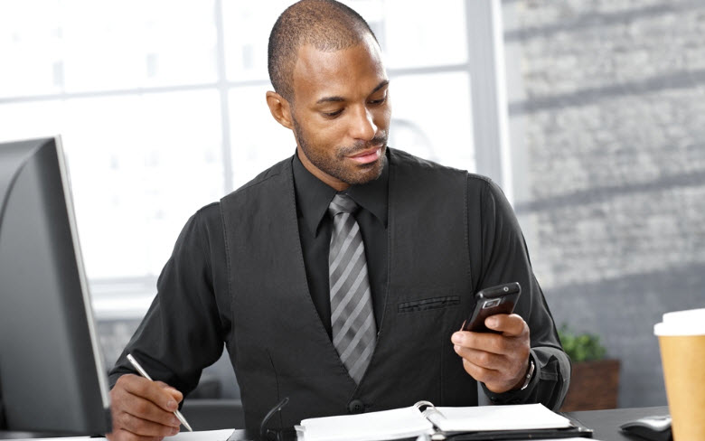 Portrait of businessman, using mobile phone