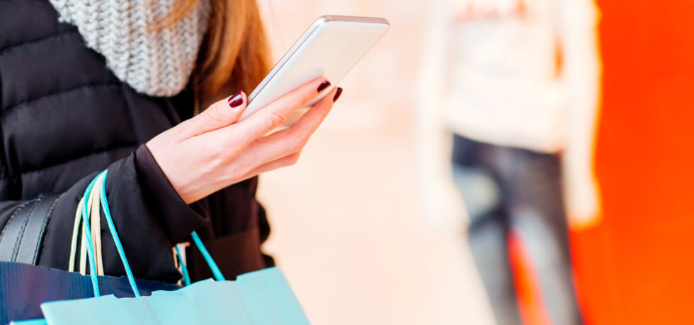 Woman with shopping bags, looking products in the mobile phone