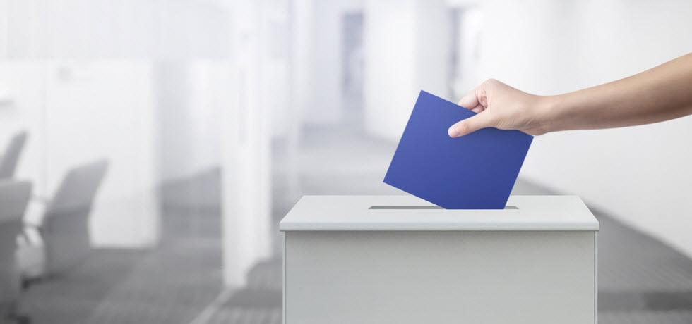Voter inserting envelope in ballot box