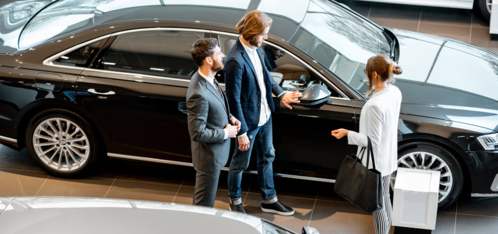 Car salesman showing a new car in a car showroom to a business couple