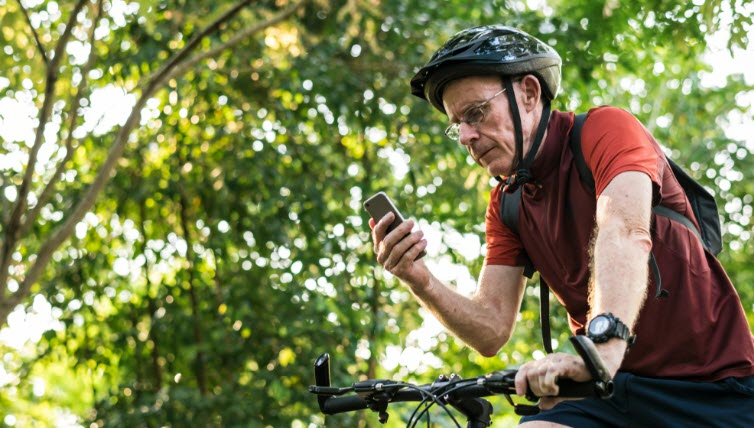 Senior cyclist reading text warning on the mobile phone