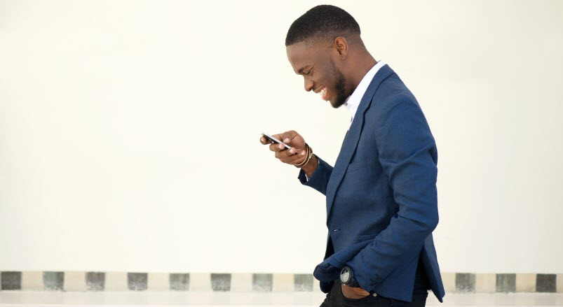 Businessman walking and sending a text message on mobile phone