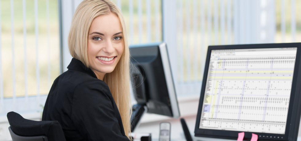 beautiful woman sitting at her desk in front of a desktop computer using customer details