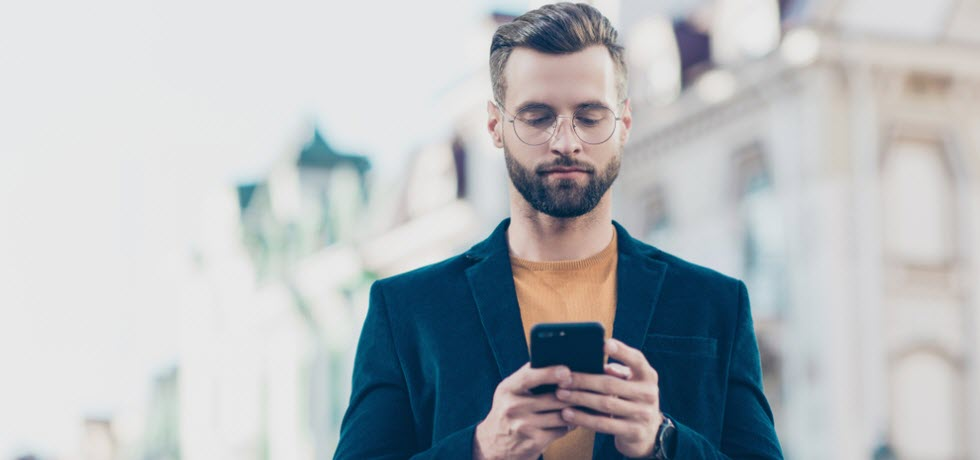 Handsome man using mobile for SMS chat