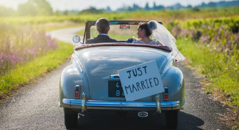 A newlywed couple driving in retro car in the countryside