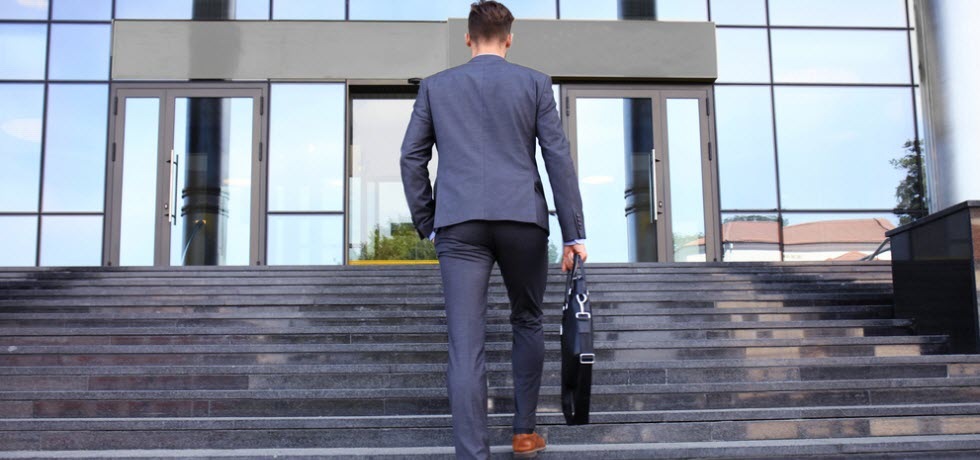 Businessman walking up the stairs towards office building