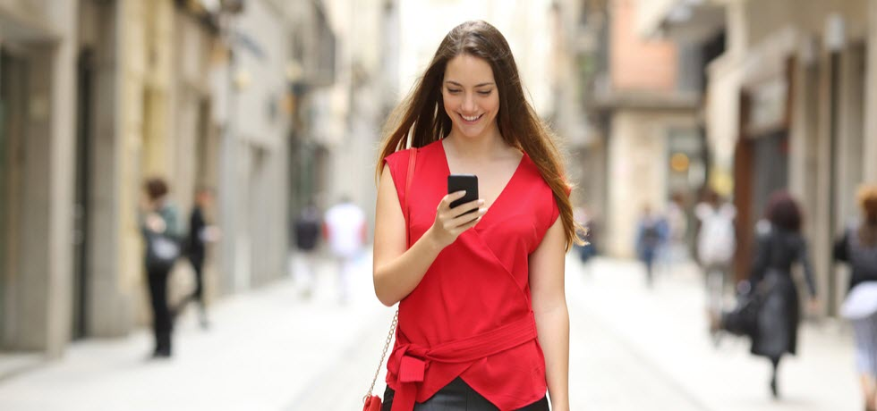 Happy woman walking in the street with mobile phone