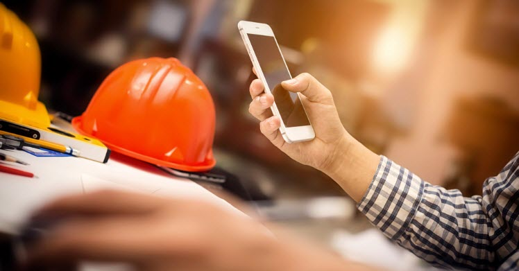 construction office desk and holding mobile smartphone