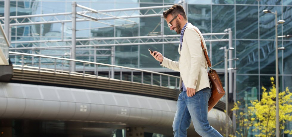 Man walking outdoors and reading a text message on his mobile phone