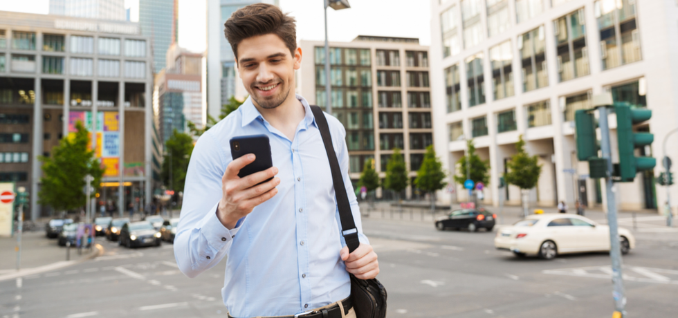 A young man reading an appointment reminder from mobile phone
