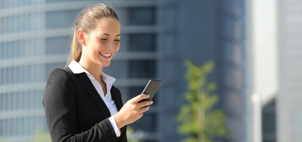 Beautiful woman with a mobile phone in the street reading text message with office buildings in the background