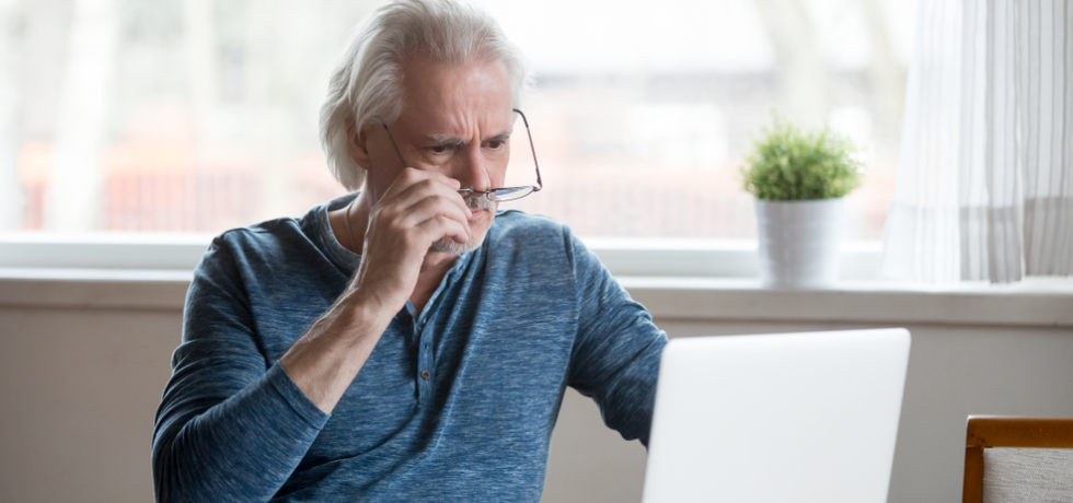 deceived frustrated senior mature man taking off glasses to look at laptop
