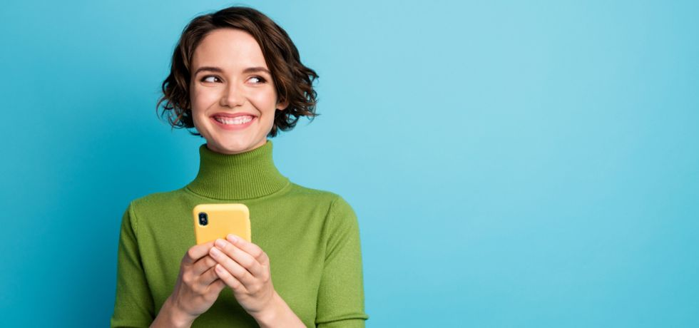 Excited woman with a mobile phone in hand