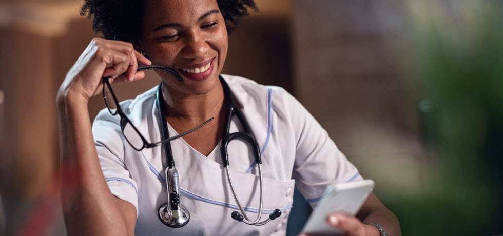 A smiling doctor reads a text message