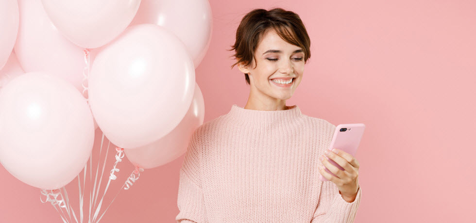 a young woman reads a birthday text message